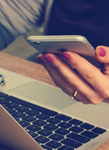 Zeigt Frau am Laptop mit Handy