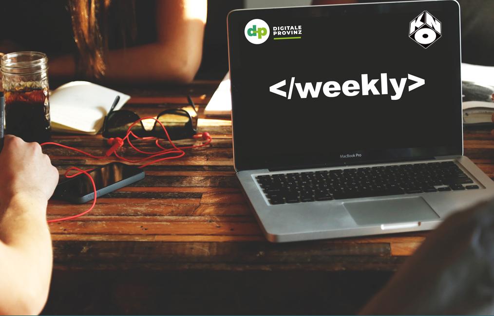 Auf dem Bild ist ein silberens MacBook Pro zu sehen, das auf einem Holztisch steht. Auf dem Bildschirm ist der Schriftzug Weekly zu lesen, links daneben steht das Digitale Provinz-Logo, rechts vom Schriftzug ist das Korrektur NachOben-Logo. Links neben dem MacBook Pro liegt eine Sonnenbrille, Kopfhörer und ein Smartphone.