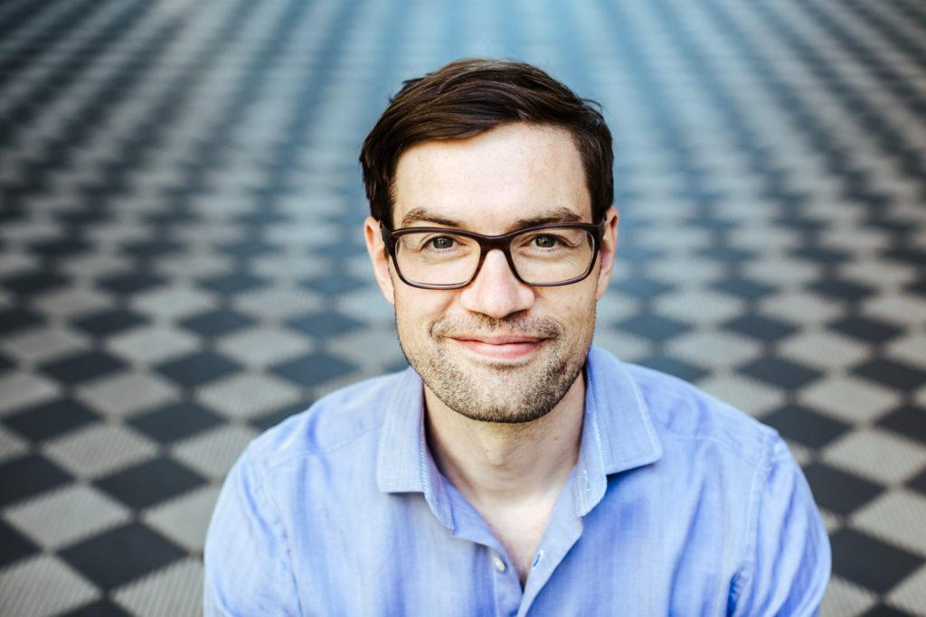 KoDorf-Mitinitiator und Summer of Pioneers-Mitbegründer Frederik Fischer trägt ein blaues Hemd und sitzt vor einem schwarz-weiß gekachelten Boden.