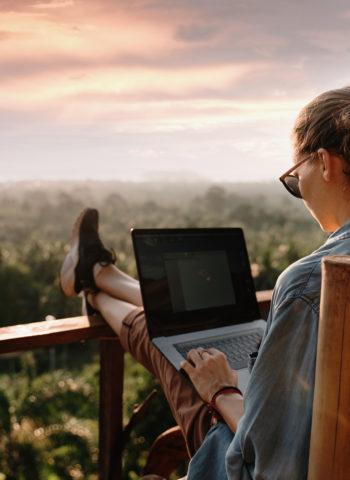 Eine junge Frau sitzt mit einem Laptop auf einem Balkon. Ihre Füße liegen auf dem Geländer. Sie trägt eine Sonnenbrille und arbeitet an dem Laptop.