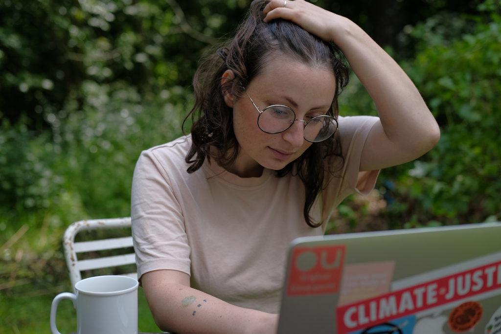 Milena Glimbovski trägt auf dem Bild ein hellrosafarbenes T-Shirt und sitzt im Grünen. Vor ihr steht ein Laptop, auf den sie schaut. Daneben steht eine weiße Kaffeetasse. Das Laptop ist mit Aufklebern wie Climate Justice und Original Unverpackt beklebt.