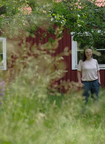 Gründerin Milena Glimbovski steht vor einem roten Haus auf dem schwedischen Land inmitten von Bäumen und Wiesen.