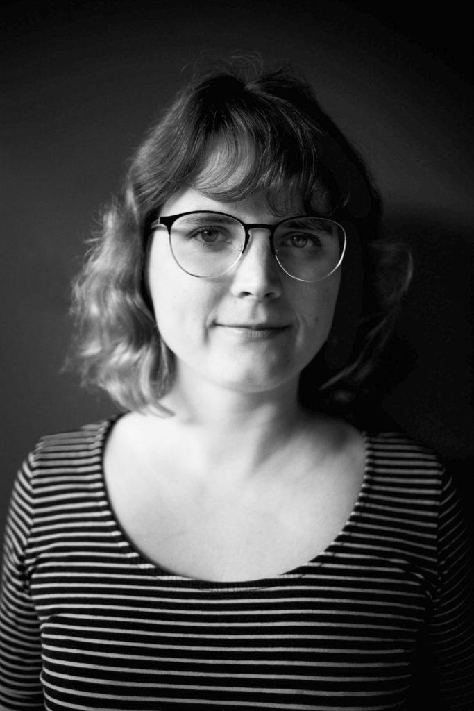 Das Bild zeigt eine Schwarz-Weiß-Fotografie von unserer Gastautorin Regine Glaß. Sie trägt ein schwarz-weiß-gestreiftes Oberteil, kinnlange wellige Haare und eine rundliche schwarz-silberne Brille.
